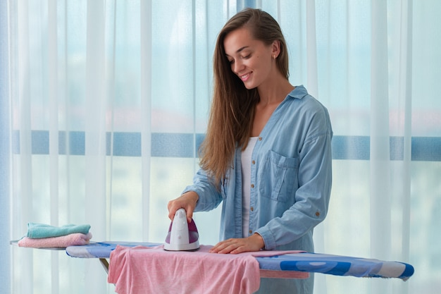Dona de casa feliz nova que passa após a lavanderia na tábua de passar