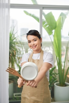 Dona de casa feliz segurando a panela, conceito de serviço de empregada doméstica