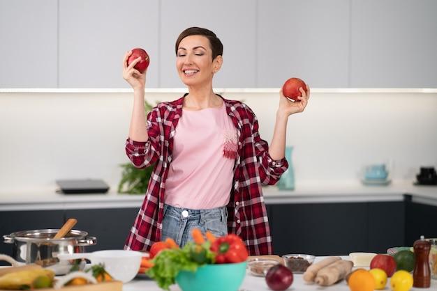 Dona de casa feliz vestindo uma camisa xadrez com um penteado curto com maçãs frescas nas mãos cozinhando uma torta de maçã