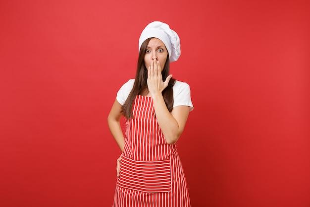 Dona de casa feminina chef cozinheira ou padeiro no avental listrado, camiseta branca, chapéu de chefs toque isolado no fundo da parede vermelha. mulher bonita dona de casa triste cobrir a boca com a palma da mão. mock-se o conceito de espaço de cópia.