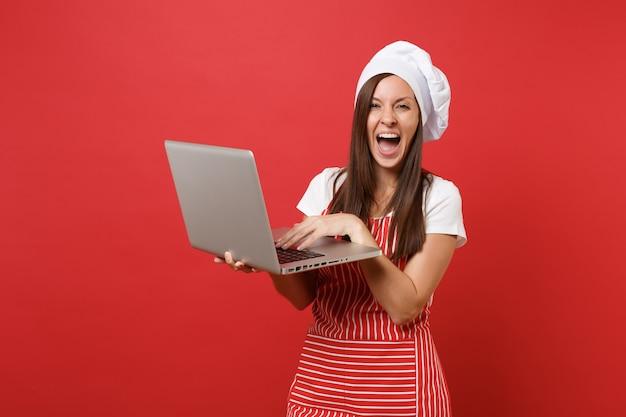 Dona de casa feminina chef cozinheira ou padeiro no avental listrado, camiseta branca, chapéu de chefs toque isolado no fundo da parede vermelha. mulher divertida governanta procurando receita no laptop pc. mock-se o conceito de espaço de cópia.