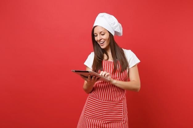 Dona de casa feminina chef cozinheira ou padeiro no avental listrado, camiseta branca, chapéu de chefs toque isolado no fundo da parede vermelha. mulher divertida governanta procurando receita no tablet pc. mock-se o conceito de espaço de cópia.