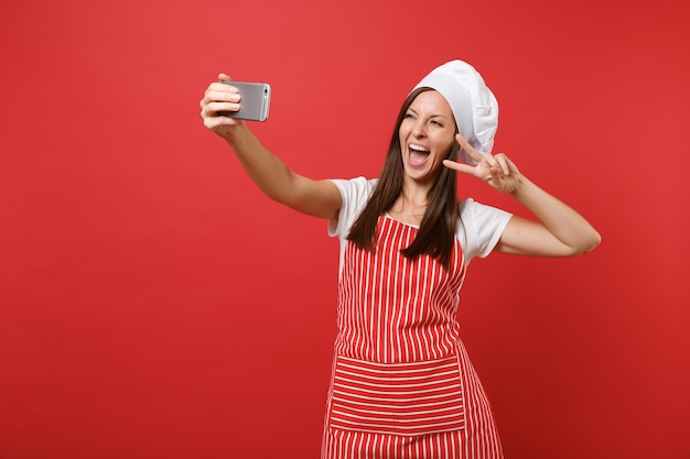 Dona de casa feminina chef cozinheira ou padeiro no avental listrado, camiseta branca, chapéu de chefs toque isolado no fundo da parede vermelha. mulher divertida sorridente fazendo selfie filmado no celular. mock-se o conceito de espaço de cópia.
