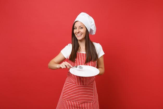 Dona de casa feminina chef cozinheira ou padeiro no avental listrado, camiseta branca, chapéu de chefs toque isolado no fundo da parede vermelha. mulher governanta segurar prato redondo vazio com garfo. mock-se o conceito de espaço de cópia.