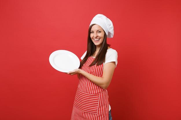 Dona de casa feminina chef cozinheira ou padeiro no avental listrado, camiseta branca, chapéu de chefs toque isolado no fundo da parede vermelha. mulher segura prato redondo em branco vazio com lugar para comida. simule o conceito de espaço de cópia