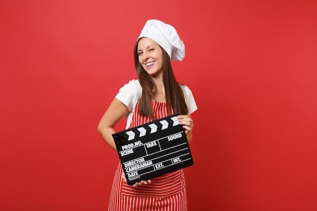 Dona de casa feminina chef cozinheira ou padeiro no avental listrado, camiseta branca, chapéu de chefs toque isolado no fundo da parede vermelha. mulher segurando claquete de fabricação de filme preto clássico. mock-se o conceito de espaço de cópia.