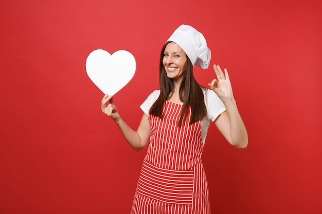 Dona de casa feminina chef cozinheira ou padeiro no avental listrado, camiseta branca, chapéu de chefs toque isolado no fundo da parede vermelha. mulher sorridente dona de casa segurar o espaço de trabalho de coração em branco. mock-se o conceito de espaço de cópia.