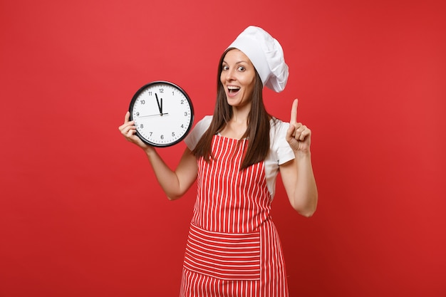 Dona de casa feminina chef cozinheira ou padeiro no avental listrado, camiseta branca, chapéu de chefs toque isolado no fundo da parede vermelha. mulher sorridente segurando na mão redondo relógio se apresse. mock-se o conceito de espaço de cópia.