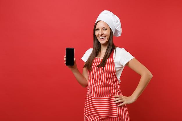 Dona de casa feminina chef cozinheira ou padeiro no chapéu de chefs avental listrado branco t-shirt toque isolado no fundo da parede vermelha. mulher segura a tela em branco do celular para conteúdo promocional simulação do conceito de espaço de cópia