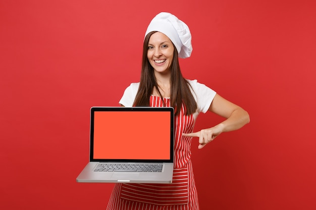 Dona de casa feminina chef cozinheira ou padeiro no chapéu de chefs avental listrado branco t-shirt toque isolado no fundo da parede vermelha. mulher segura a tela em branco do laptop para conteúdo promocional simulação do conceito de espaço de cópia