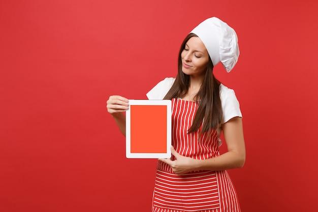 Dona de casa feminina chef cozinheira ou padeiro no chapéu de chefs avental listrado branco t-shirt toque isolado no fundo da parede vermelha. mulher segura a tela em branco do tablet pc para conteúdo promocional simulação do conceito de espaço de cópia