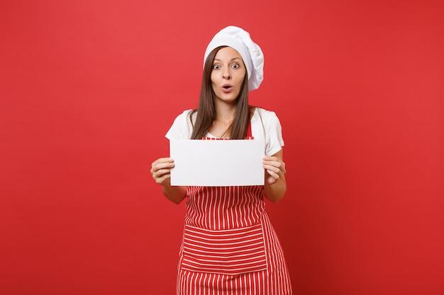 Dona de casa feminina chef cozinheira ou padeiro no chapéu de chefs avental listrado branco t-shirt toque isolado no fundo da parede vermelha. mulher segura placa de sinalização em branco, lugar para texto promocional. mock-se o conceito de espaço de cópia.