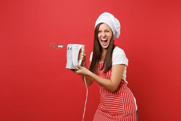 Dona de casa feminina chef cozinheira ou padeiro no chapéu de chefs avental listrado branco t-shirt toque isolado no fundo da parede vermelha. mulher segurar a batedeira, cozinhar biscoito de gengibre de natal. mock-se o conceito de espaço de cópia.