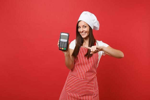 Dona de casa feminina chef cozinheira ou padeiro no chapéu de chefs de t-shirt toque avental listrado isolado no fundo da parede vermelha. mulher segura na mão dispositivo nfc terminal de pagamento de banco sem fio. mock-se o conceito de espaço de cópia.
