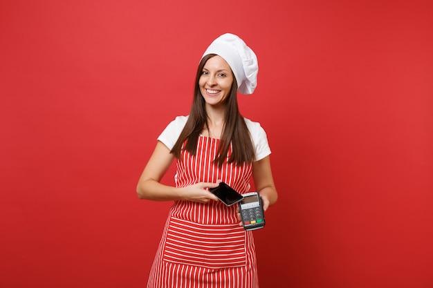 Dona de casa feminina chef cozinheira ou padeiro no chapéu de chefs de t-shirt toque avental listrado isolado no fundo da parede vermelha. mulher segura na mão o terminal de pagamento do banco, dispositivo de telefone móvel. mock-se o conceito de espaço de cópia.