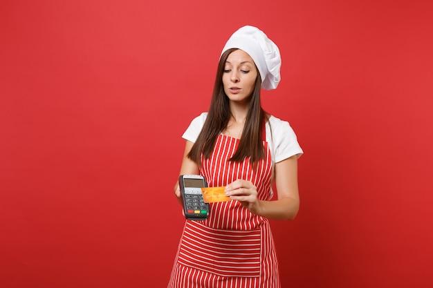 Dona de casa feminina chef cozinheira ou padeiro no chapéu de chefs de t-shirt toque avental listrado isolado no fundo da parede vermelha. mulher segura na mão terminal de pagamento do banco, cartão de crédito, dispositivo nfc simulação do conceito de espaço de cópia