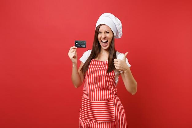 Dona de casa feminina chef cozinheiro padeiro no chapéu de chefs avental listrado branco t-shirt toque isolado no fundo da parede vermelha. mulher excitada segura na mão o cartão do banco de crédito, dinheiro sem dinheiro. simule o conceito de espaço de cópia