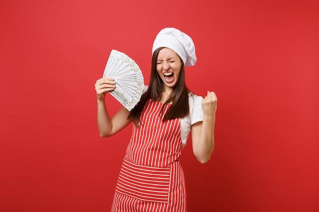 Dona de casa feminina chef cozinheiro padeiro no chapéu de chefs avental listrado branco t-shirt toque isolado no fundo da parede vermelha. mulher excitada segurando lotes de notas de dólares em dinheiro. mock-se o conceito de espaço de cópia.