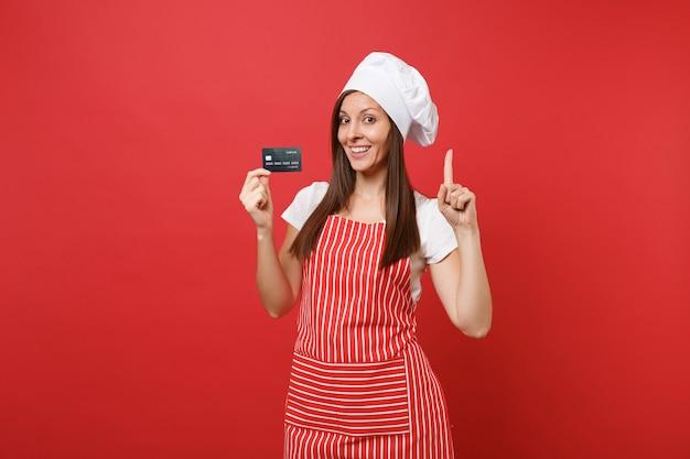 Dona de casa feminina chef cozinheiro padeiro no chapéu de chefs avental listrado branco t-shirt toque isolado no fundo da parede vermelha. mulher sorridente segura na mão o cartão do banco de crédito, dinheiro sem dinheiro. simule o conceito de espaço de cópia