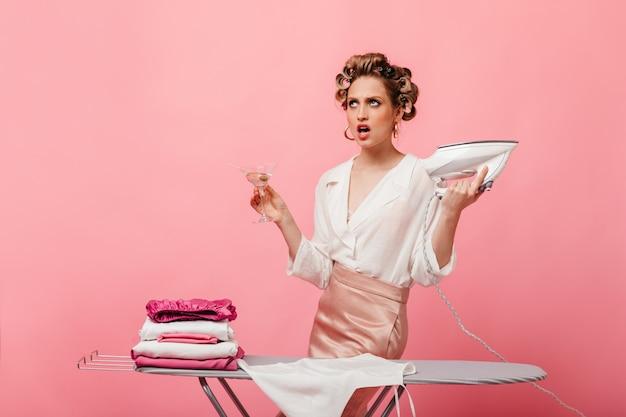 Dona de casa irritada em uma linda roupa segurando uma taça de martini e passando roupas na parede rosa