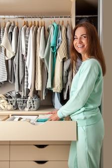 Dona de casa jovem caucasiana segurando o recipiente com meias, calcinhas e cuecas. armazenamento de roupas.