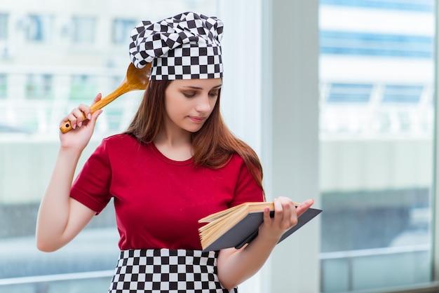 Dona de casa jovem, referindo-se ao livro de receitas