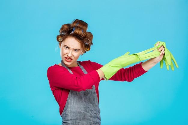 Dona de casa jovem tira as luvas de borracha verde após um longo dia