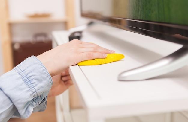 Dona de casa limpando a poeira do suporte da tv na sala de estar