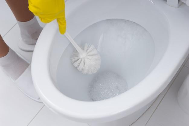 Dona de casa limpando o banheiro do banheiro com uma escova e detergente antibacteriano, vista de perto do vaso sanitário