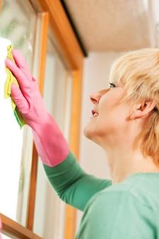 Dona de casa limpando suas janelas em luvas de borracha