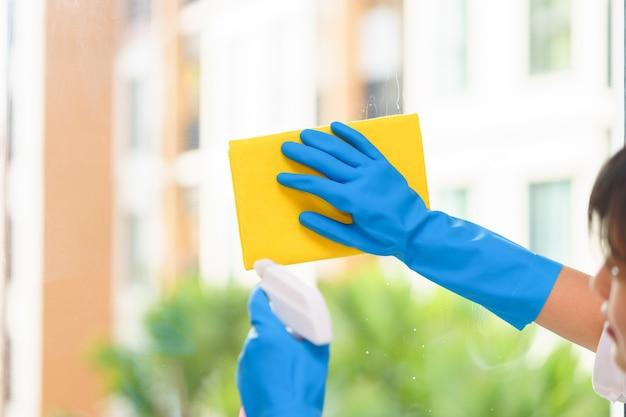Dona de casa limpeza de espelho com pano amarelo