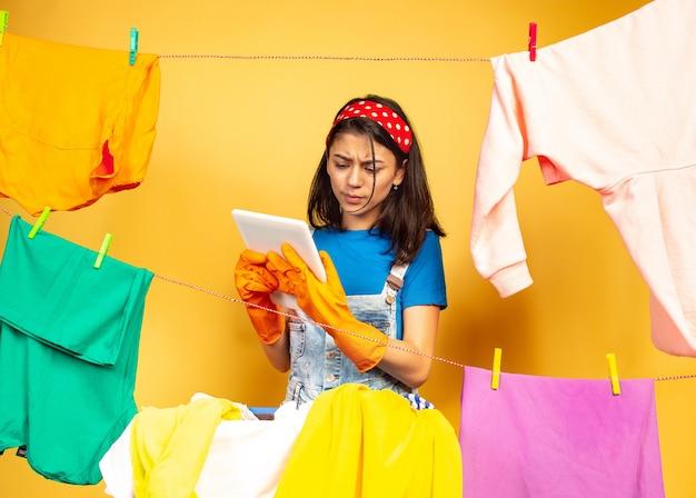 Dona de casa linda e engraçada fazendo trabalhos domésticos isolados no espaço amarelo. jovem mulher caucasiana rodeada de roupas lavadas