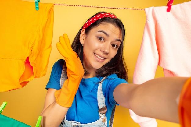 Dona de casa linda e engraçada fazendo trabalhos domésticos isolados no fundo amarelo. jovem mulher caucasiana, rodeada de roupas lavadas. vida doméstica, arte brilhante, conceito de limpeza. visualização de selfie.