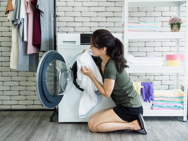 Dona de casa linda jovem asiática sentada com toalha limpa branca sorrindo e cheirando após a lavagem da máquina de lavar na lavanderia.