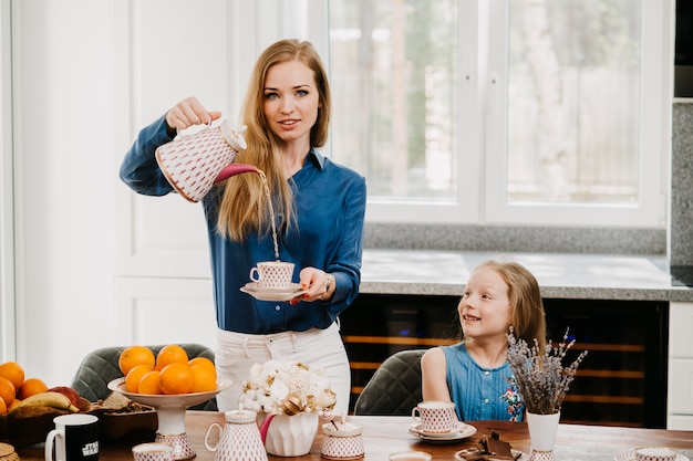 Dona de casa linda ruiva na camisa azul e calça branca na cozinha