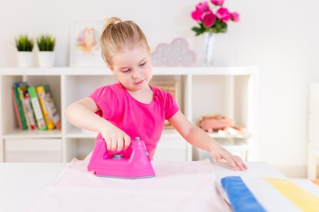 Dona de casa loira bebê menina brincando com ferro de brinquedo-de-rosa. ironong roupas sobre uma mesa branca. trabalho doméstico, ajudante