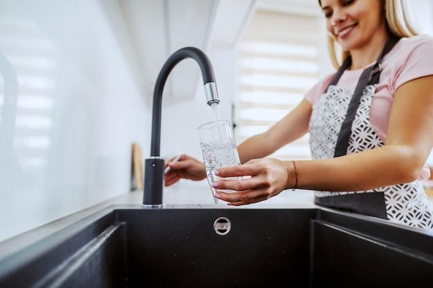 Dona de casa loira em pé na cozinha e derramando água da pia.
