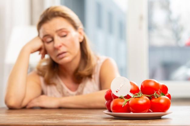 Dona de casa loira sentada à mesa olhando tomates, mas com alergia