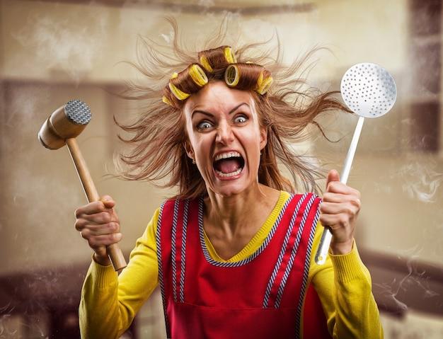 Dona de casa louca com utensílios de cozinha