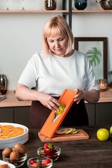 Dona de casa madura cortando peras verdes frescas na mesa da cozinha enquanto prepara várias frutas para o inverno no ambiente doméstico