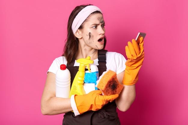 Dona de casa morena esbelta e chocada segura garrafas de detergente em uma mão e telefone em outra