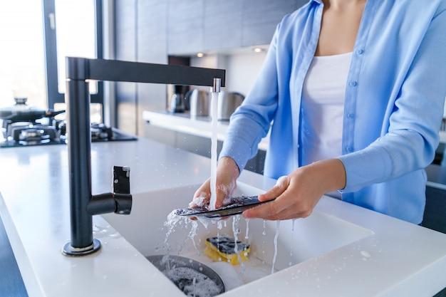 Dona de casa mulher da limpeza lavar a louça após o jantar na cozinha