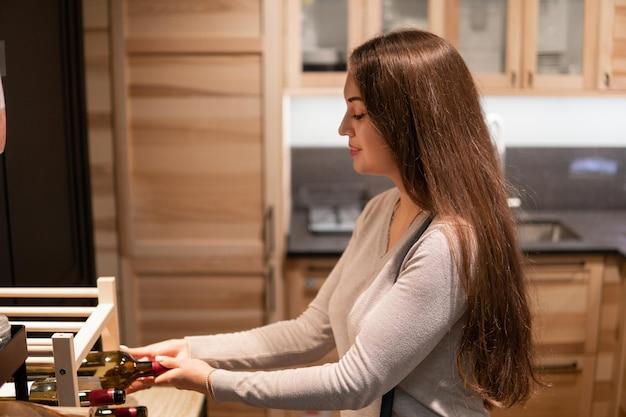 Dona de casa mulher leva garrafa de vinho na moderna cozinha de madeira em casa. ela tem cabelo comprido