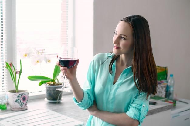 Dona de casa na cozinha com um copo de vinho tinto, olhando pela janela