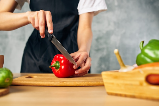 Dona de casa na cozinha cortando dieta de salada de legumes