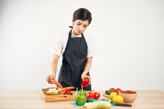 Dona de casa na cozinha cortando dieta de vegetais
