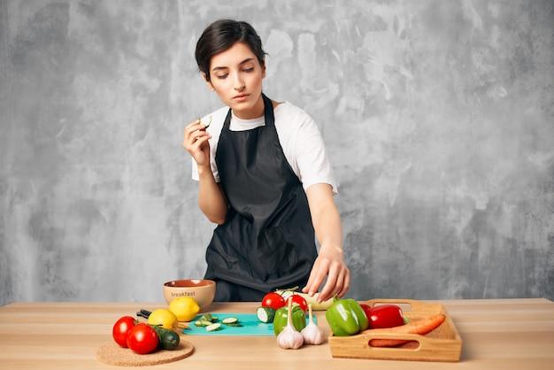 Dona de casa na cozinha cortando legumes na tábua