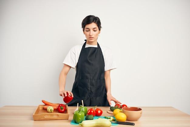 Dona de casa na cozinha cortando salada de legumes