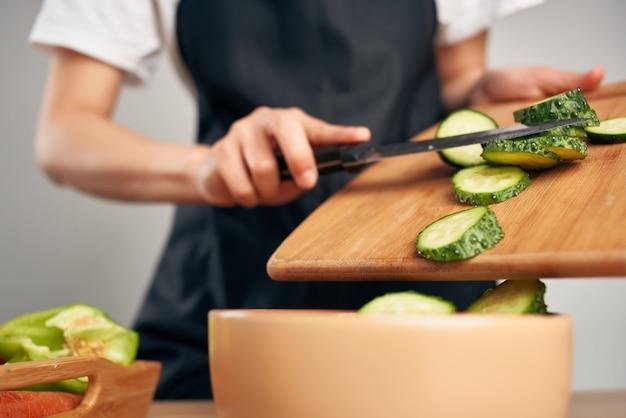Dona de casa na cozinha cortando vegetais comendo vitaminas saudáveis