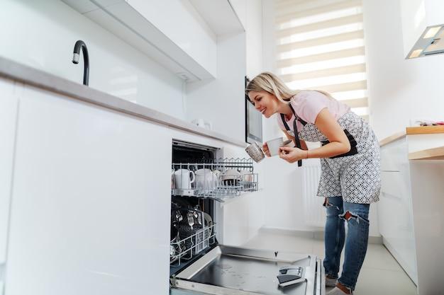 Dona de casa no avental colocando canecas na máquina de lavar louça.